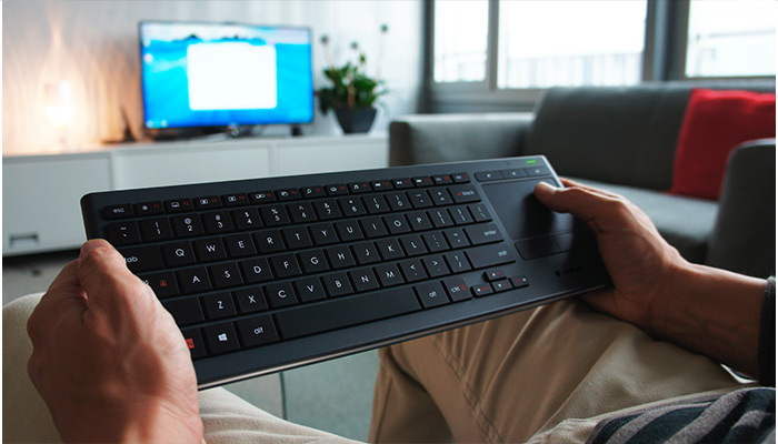 Man holding K830 keyboard in living room setting