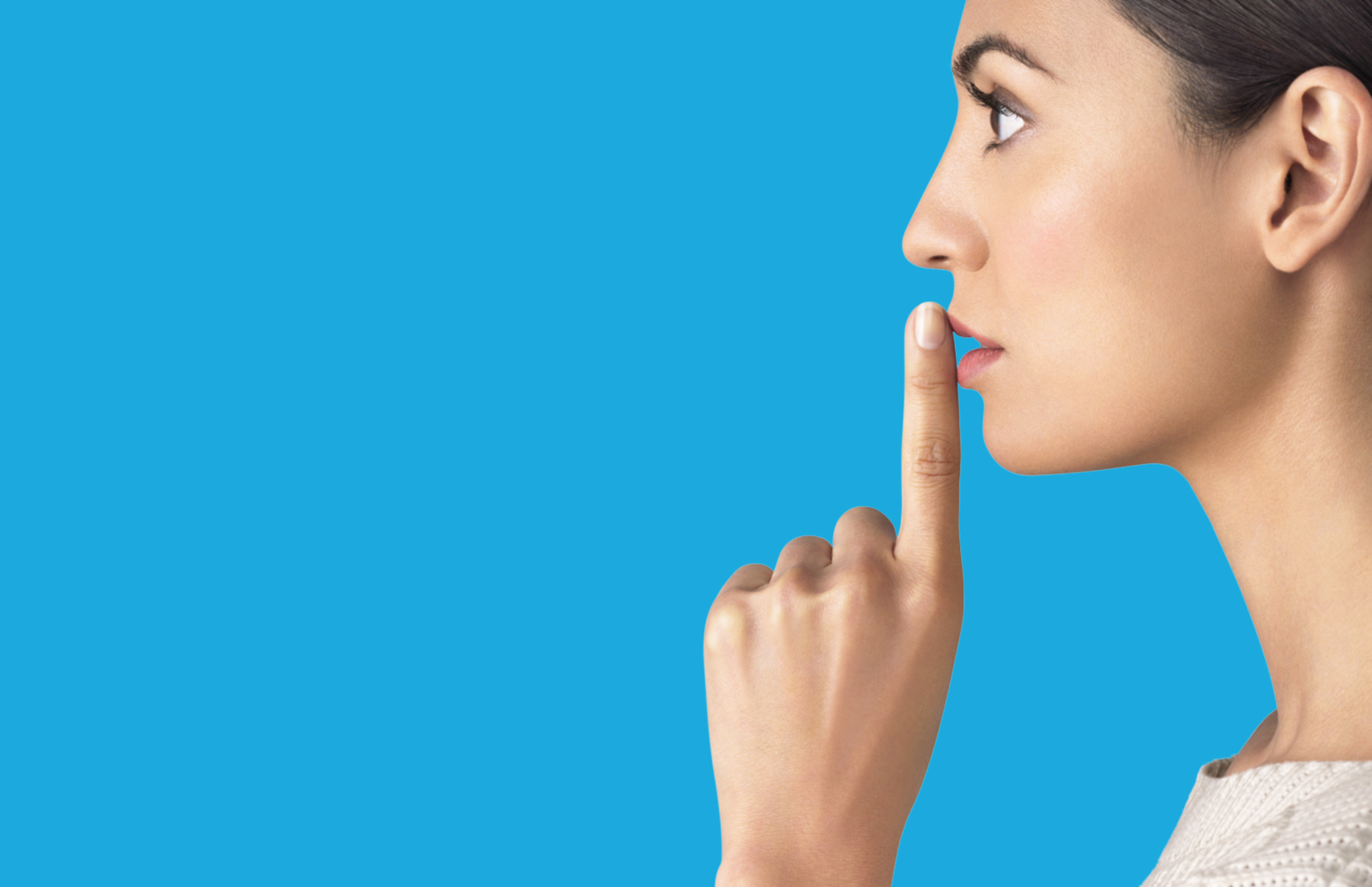 Image of Woman placing finger to mouth to request silence