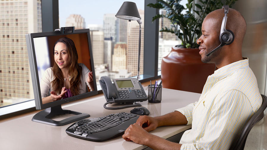 Man video conferencing on his desk