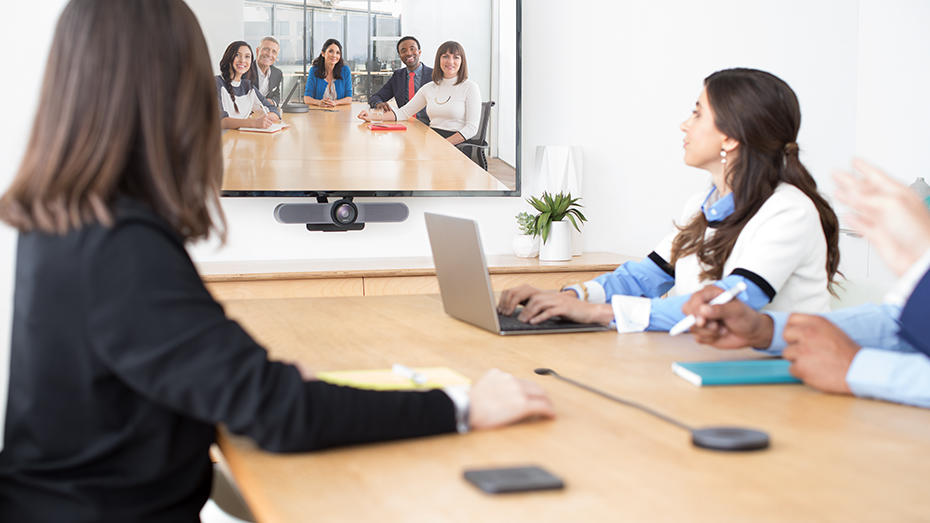 People at conference table video conferencing