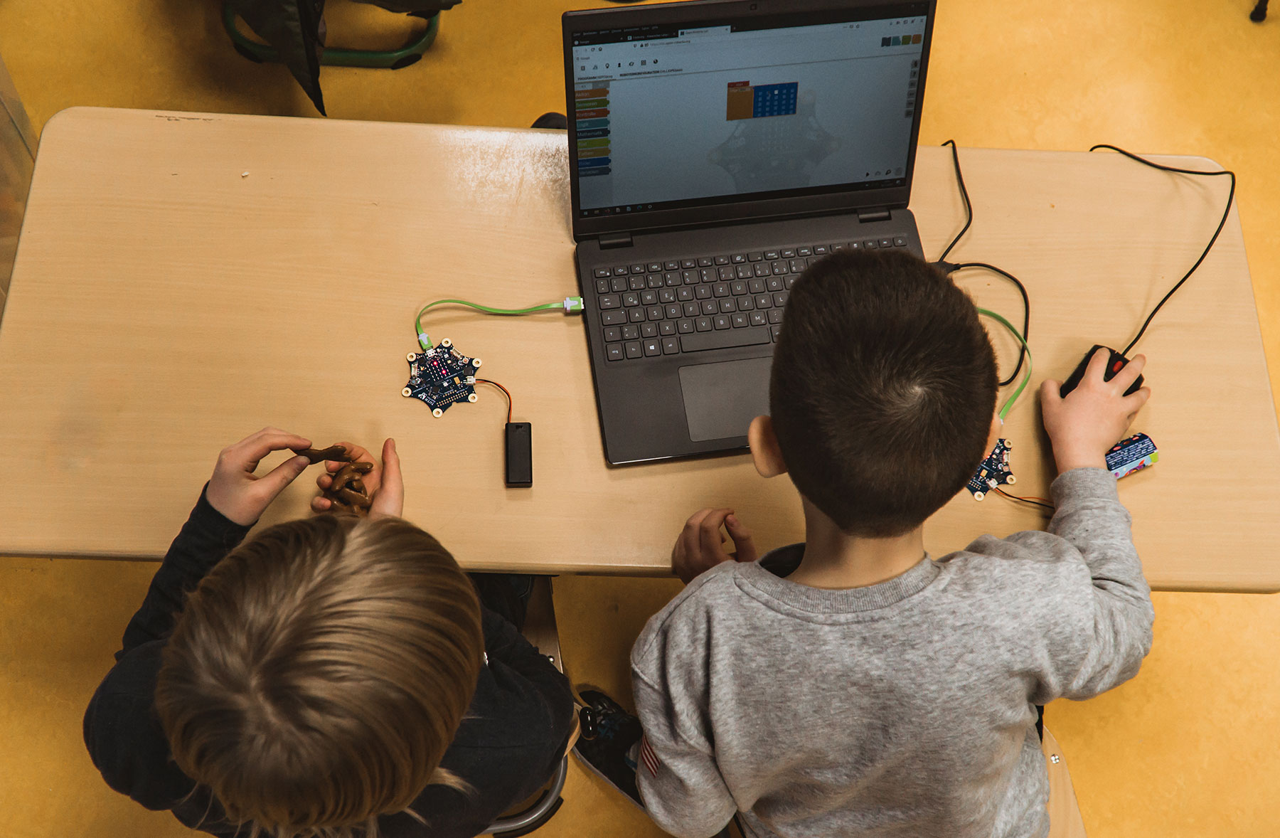 Children using laptop with a mouse connected