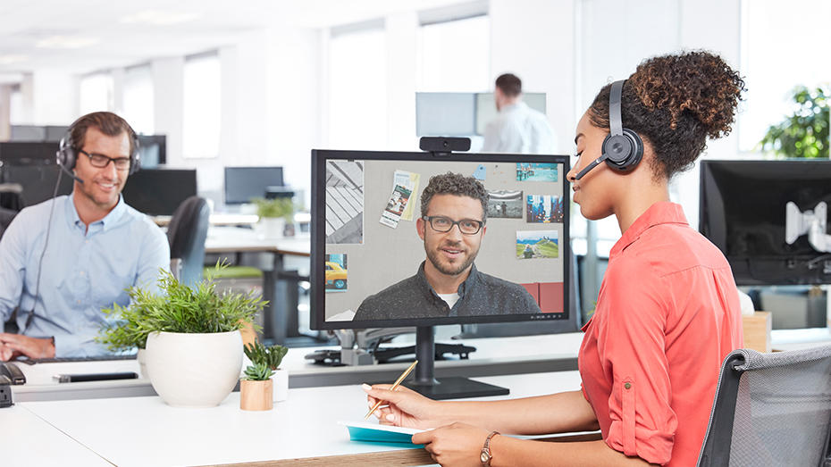 Woman working in office and video conferencing with wireless headset